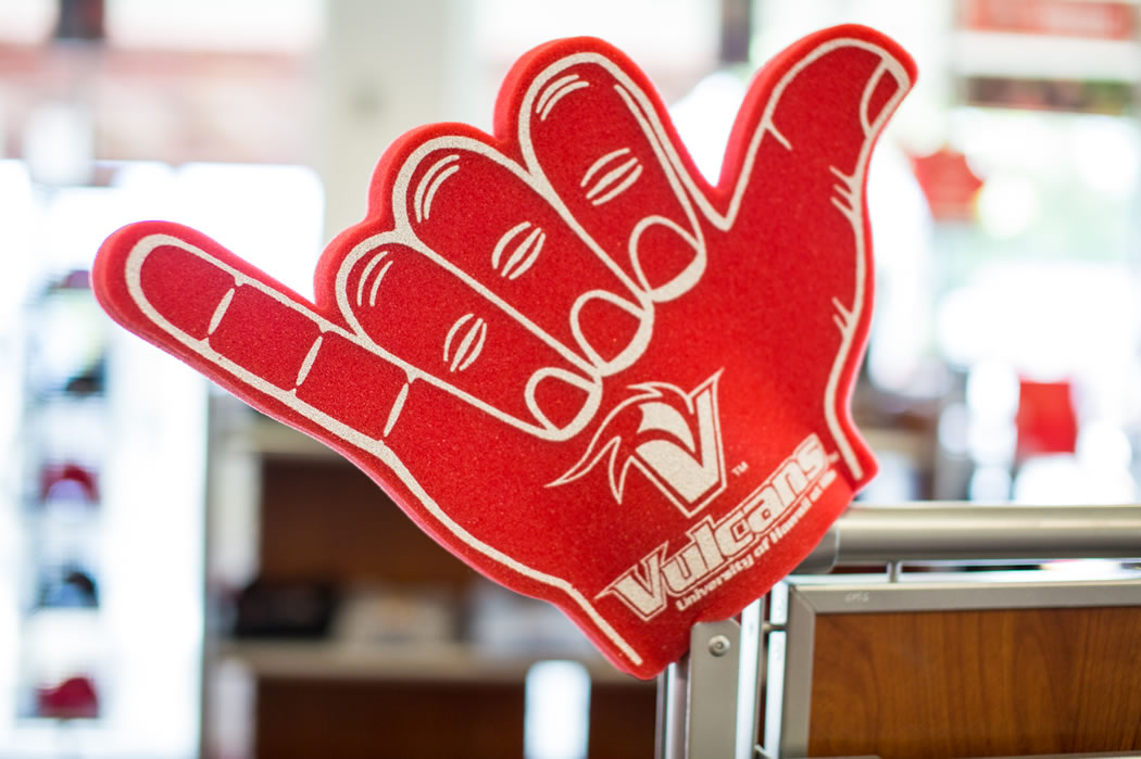 An oversided red foam shaka hand imprinted with the Vulcans logo