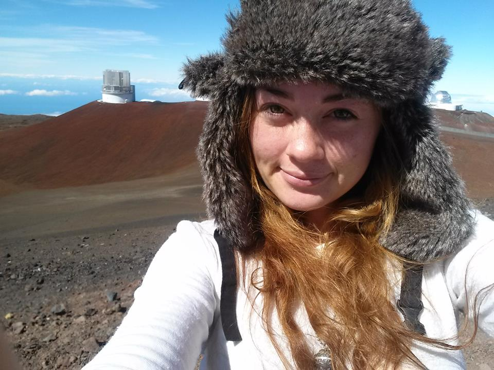 Ashley smiling on Mauna Kea's summit with telescopes in the background