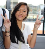 Jamae sits on a bus and gives two peace signs