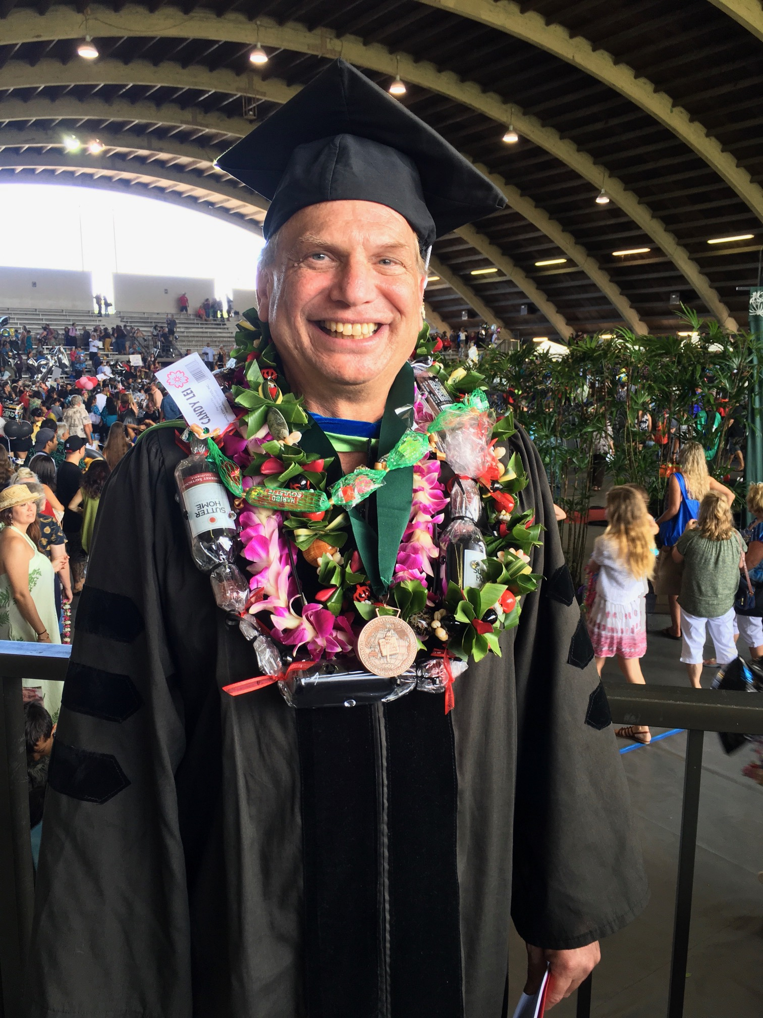 Dr. Adam Pack stands in the Edith Kanakaole stadium, adorned with lei