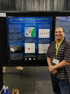 Dr. Adam Pack stands next to his poster on Humpback Whale movement