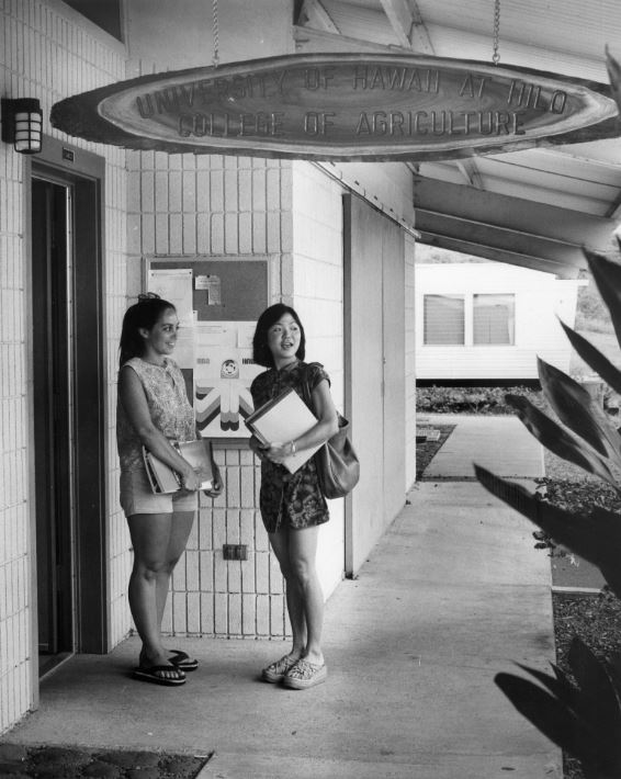Two students stand under sign reading: University of Hawaii at Hilo College of Agriculture.