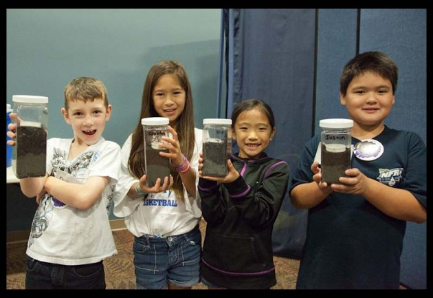Second and third graders show off their mini-ecosystems.