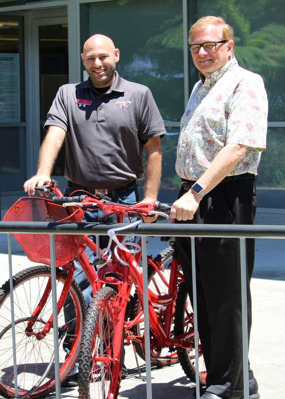 Jake Picus (l), associate director New Student Programs, and Don Straney (r), chancellor, stand with two of the red Bike Share Program bicycles.