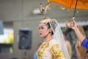 Woman in traditional Filipino attire, yellow brocade with ornate headdress, umbrella held overhead by attendant.
