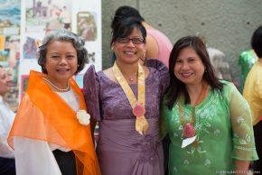Three women in traditional Filipino attire: orange, lavender and green colors.