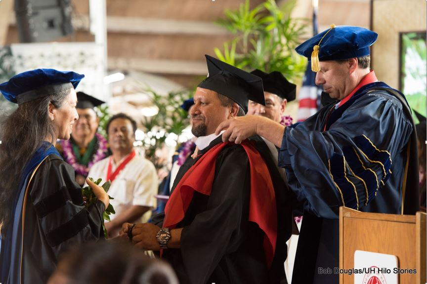 Professor places hood on graduate's shoulders.