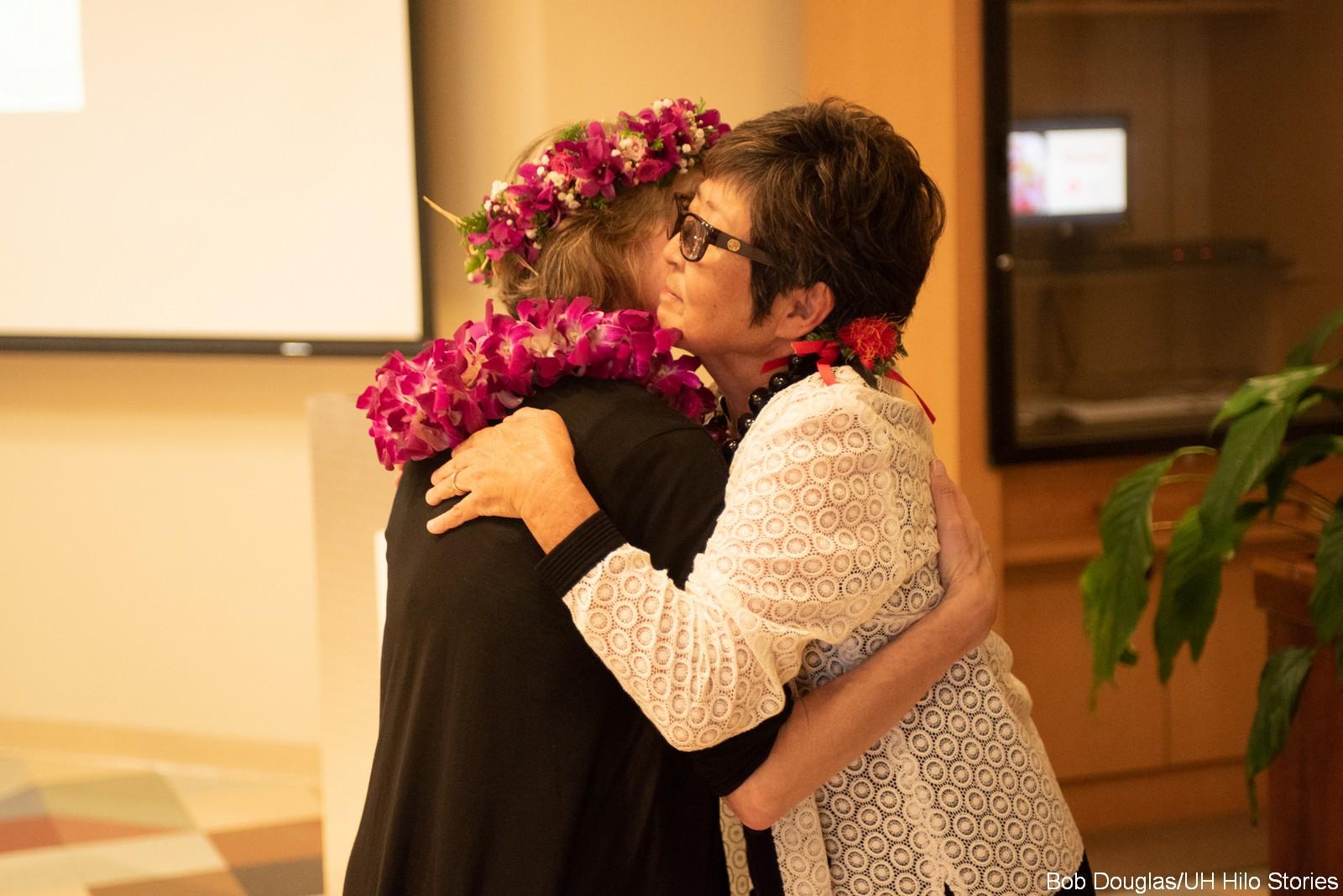 Marcia Sakai hugs Jennifer Doudna.