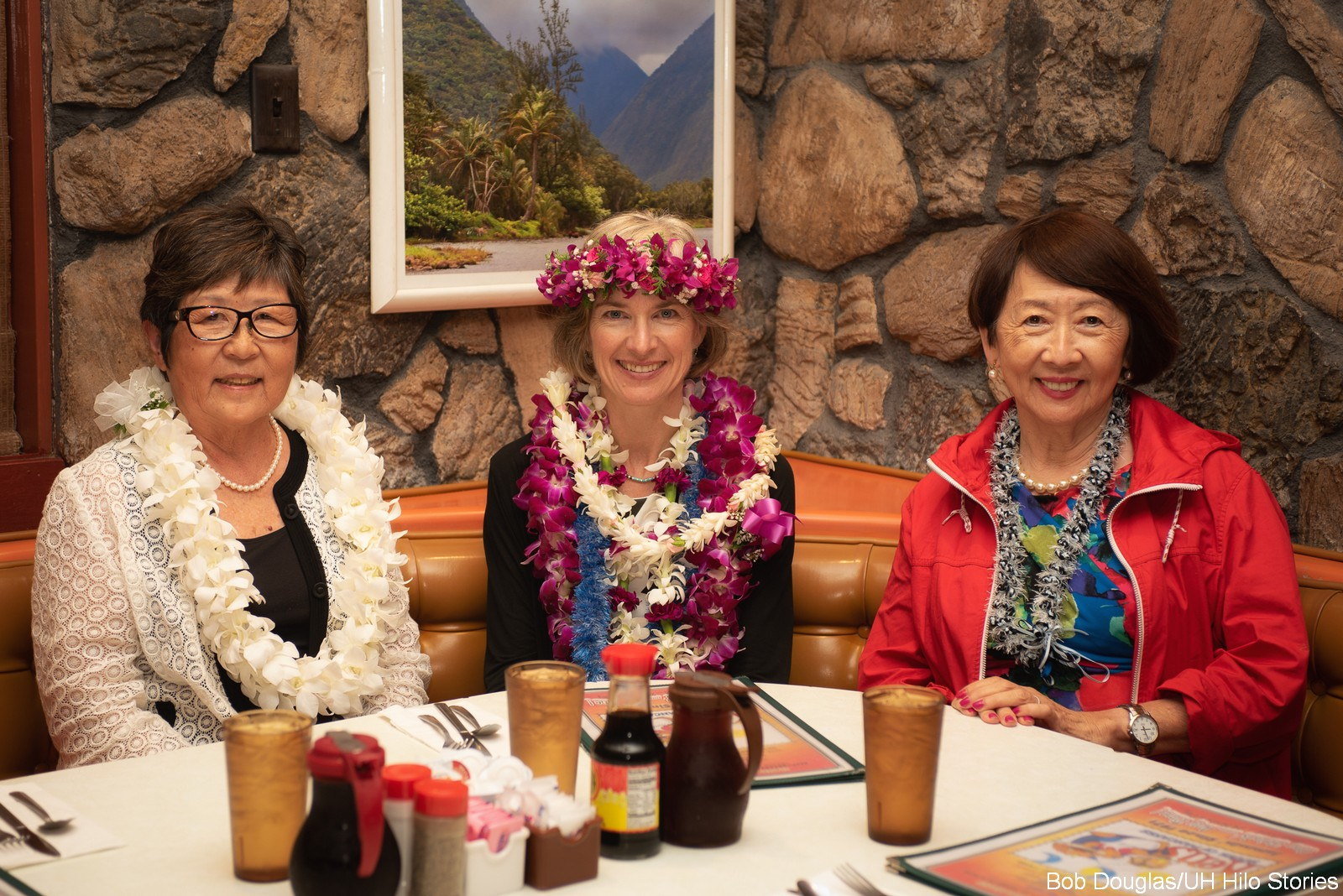 Marcia Sakai, Jennifer Doudna and Rose Tseng at dinner table with lava wall background.