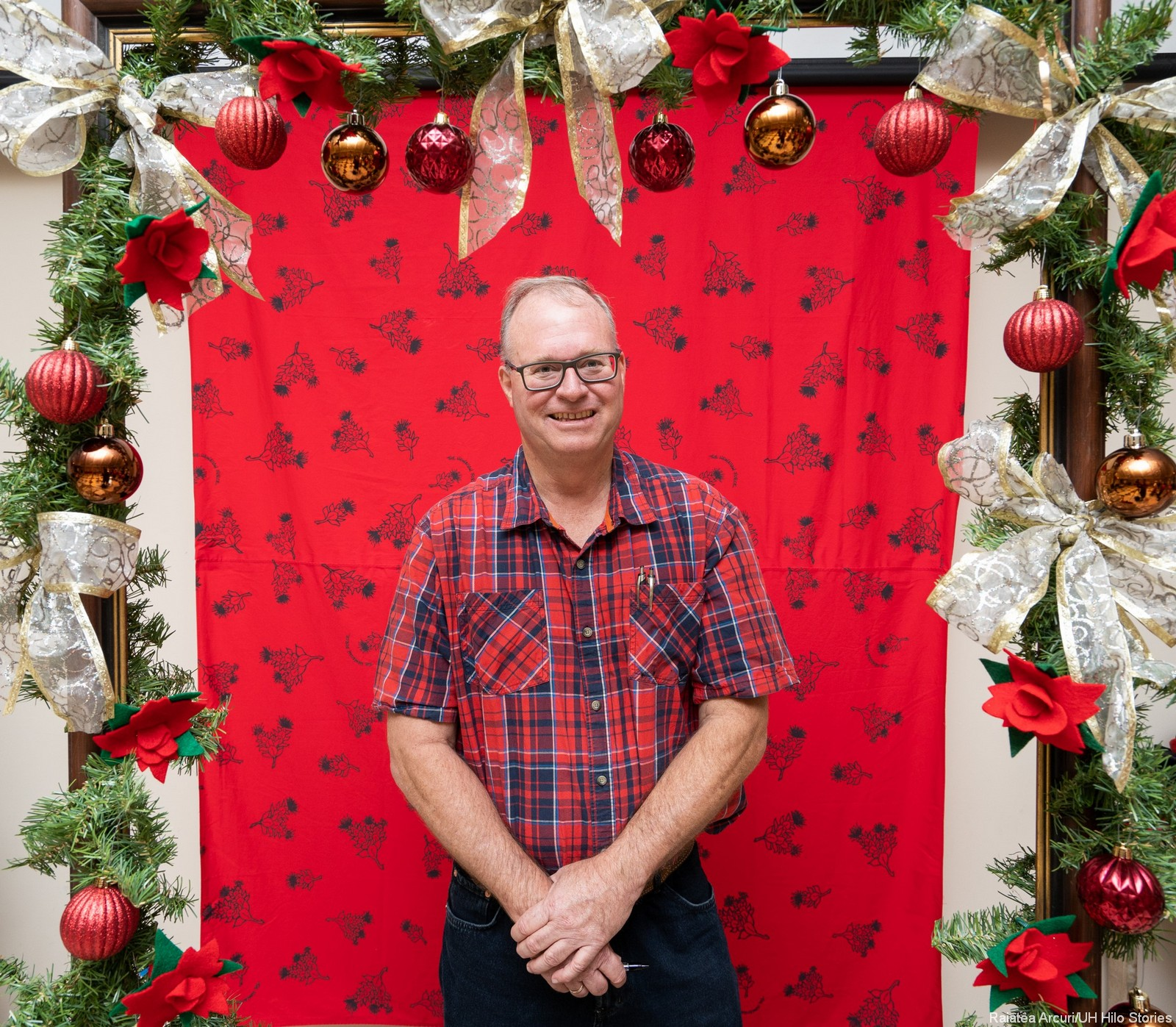 Faculty/staff/admin in Christmas costumes, standing behind a picture frame decorated with pine and bows. It's a silly, fun photo booth thing!