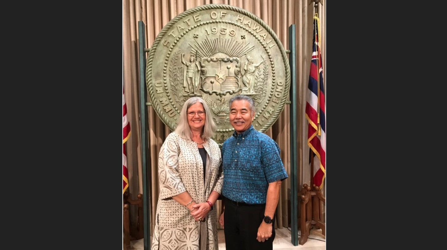 Chancellor Irwin and Gov. Ige stand for photo under state seal.