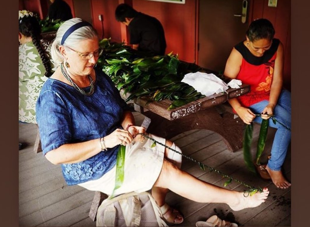 Chancellor making ti-lef lei, holding braid with her toes and weaving length of ti.