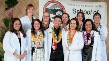 Nursing cohort in white coats pose for photo.
