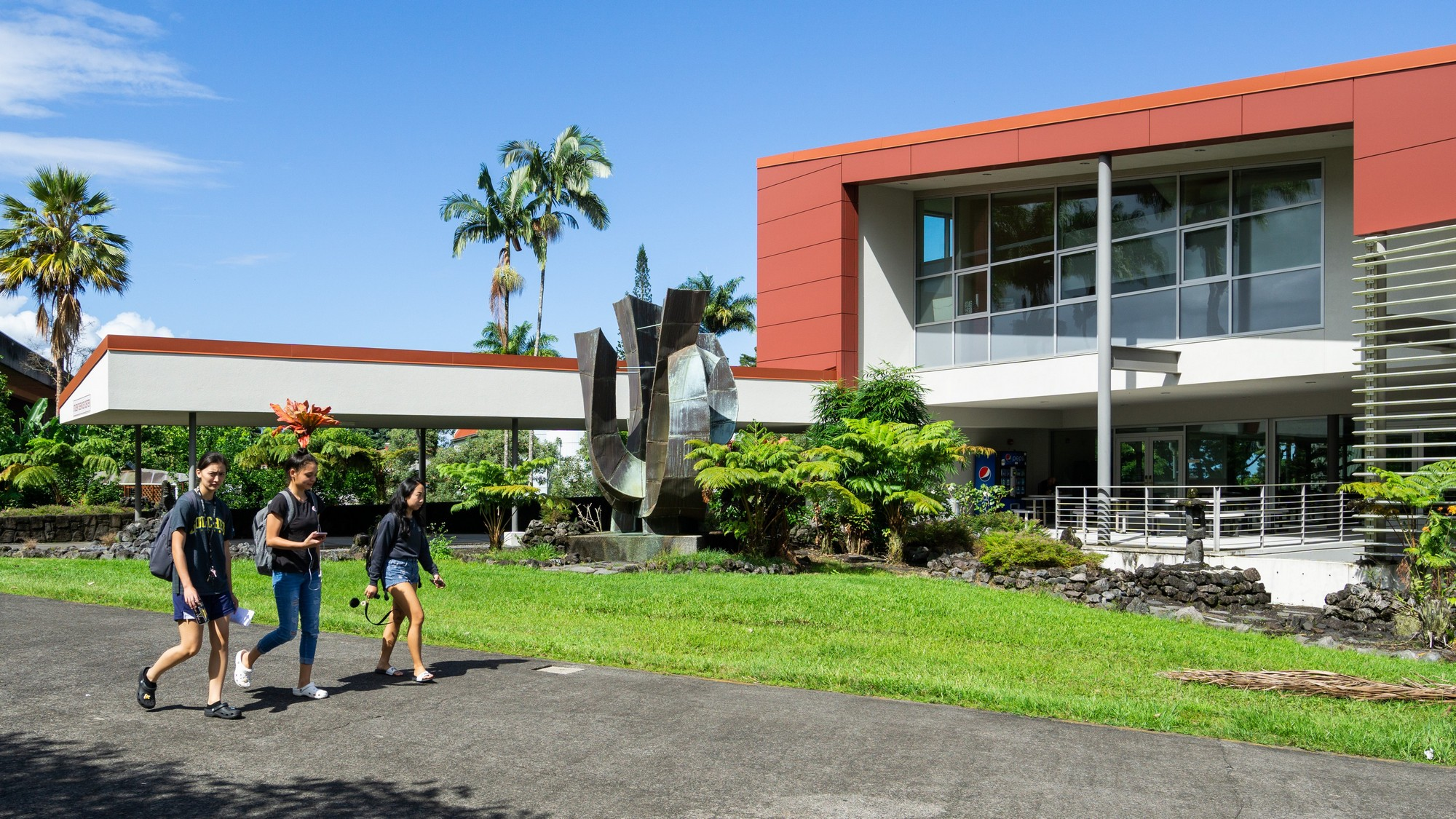 Three students walking by the Student Services Building