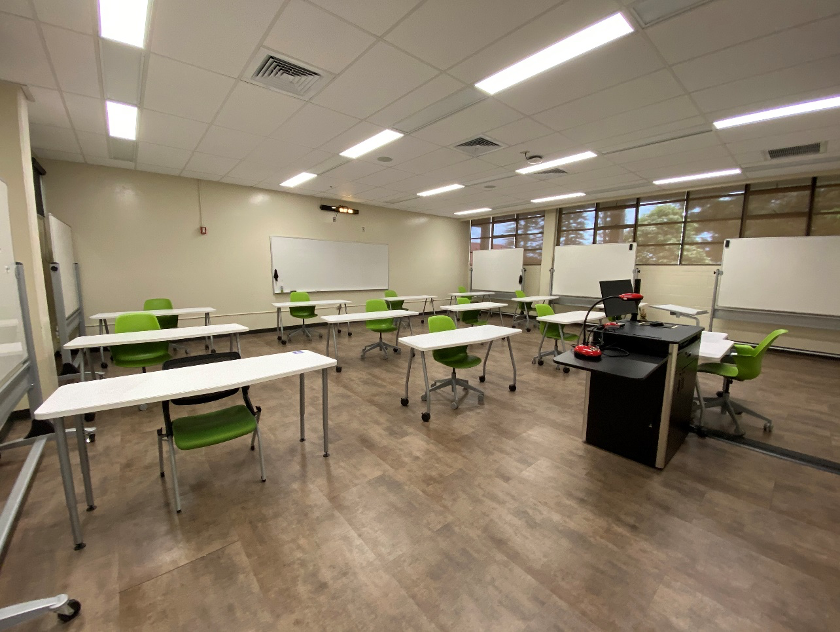 Large desks spaced out in classroom.