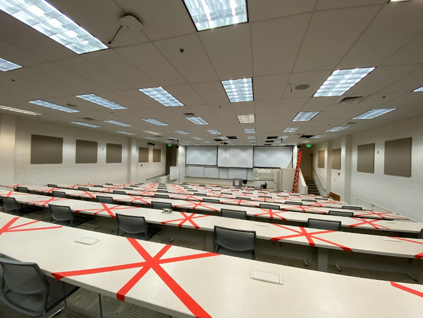 Classroom with red tape x-ing out seats that need to remain empty.