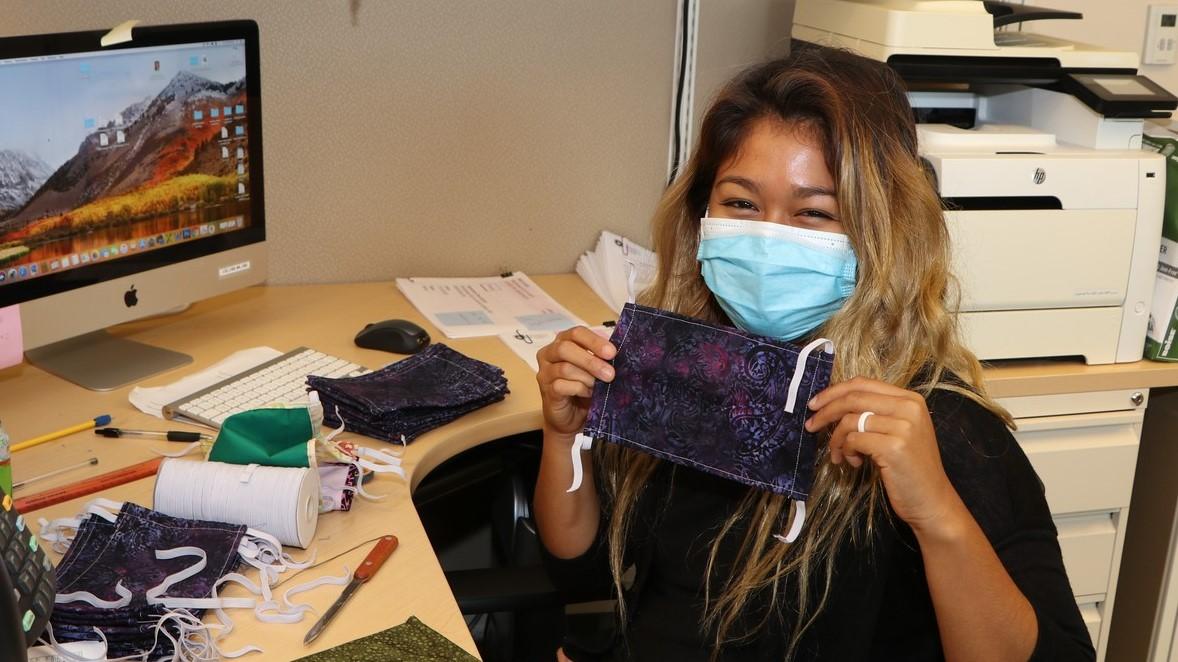 Office worker at desk wears mask.