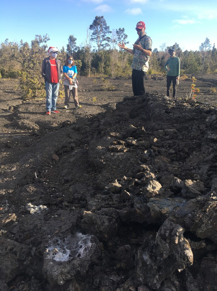 Group of people stand near a lava outcrop.