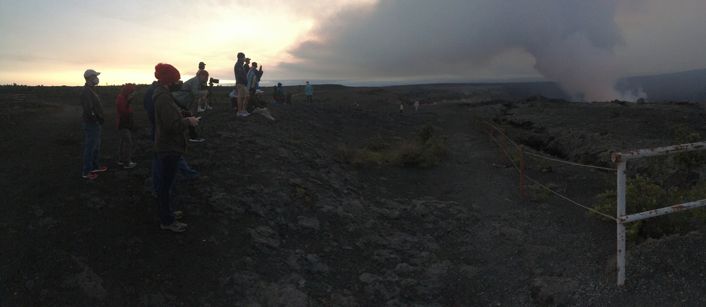 As it gets dark, a group of people view plume from eruption.