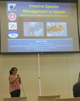 Darcy Yogi gives her presentation. PowerPoint slide up on large screen above her head, words: Invasive Species Management in Hawaii with a focus on Mauna Kea & Little Fire Ants.
