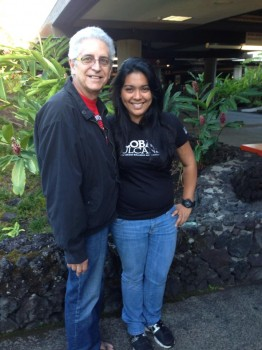 Ishael and her Papa stand in front of greenery and a low rock wall, posing for photo.