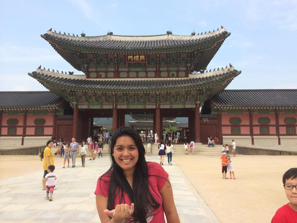 Ishael gives the shaka while standing in front of temple.