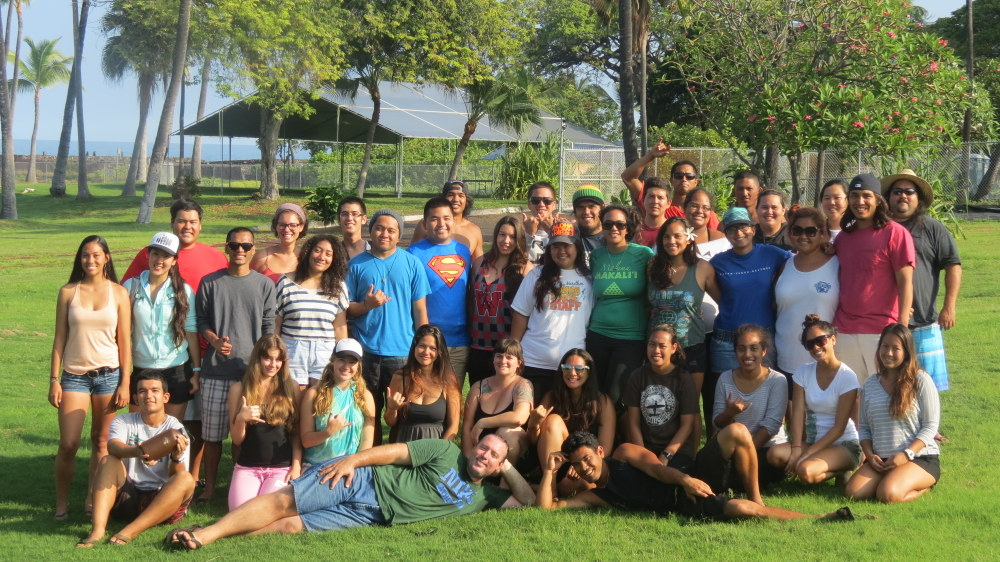 2014 summer intership cohort poses for group photo at park at Hilo Bay, on grassy area, trees and ocean in background.