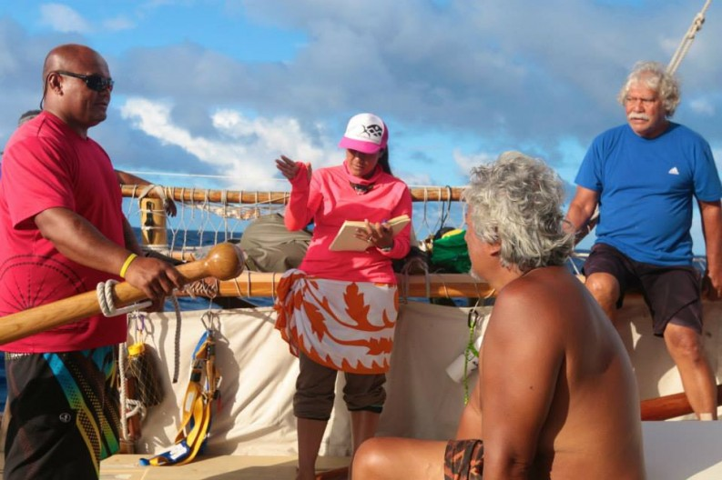 On board, Cesi speaks to crew. She is holding and looking at/reading from a book.