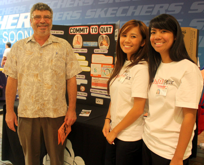 Edward Fisher stand with two students for photo at the UH Hilo booth.