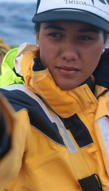 "Celeste Manuia ""Cesi"" Ha'o aboard voyaging canoe. Cap and all-weather jacket, ocean in background."