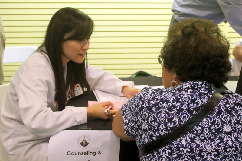 Student in white coat counseling woman at fair.