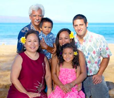 Keiki and her family, formal photo taken at the beach, ocean in background.