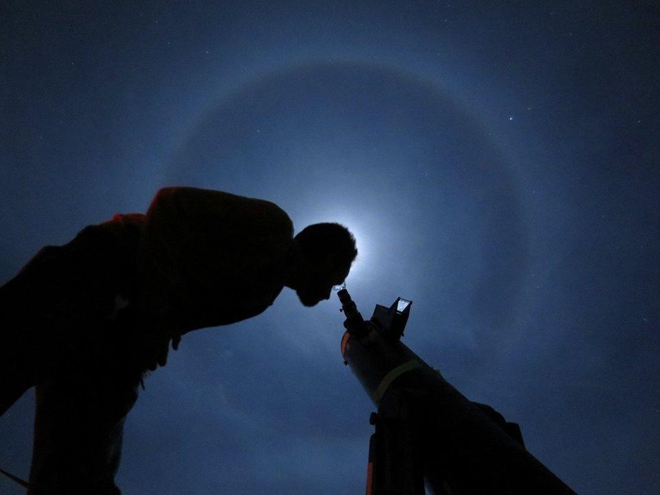 Wilfred Tyler Gee looking through telescope.