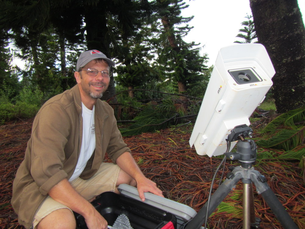 UH Hilo researcher Marcos Gorresen in forest with thermal camera used to monitor bat behavior at night.