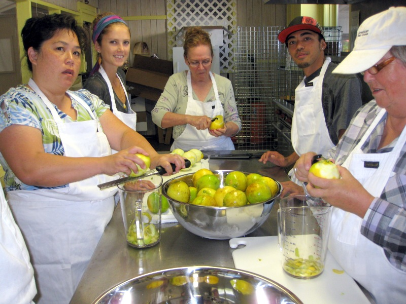 Five students in commercial kitchen, fixing food, cutting citrus.