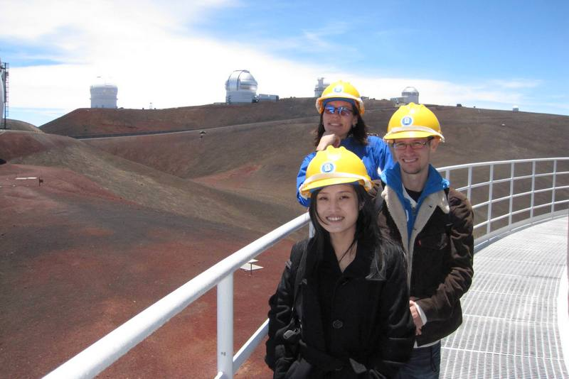 Kathy and two students stand on the catwalk with other observatories in the background.
