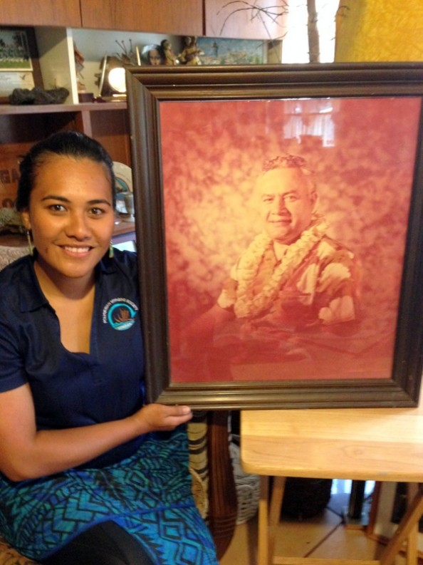 Cesi, seated, holds large framed photo of her grandfather. The photo is colored in a monotone reddish brown. He is wearing lei.