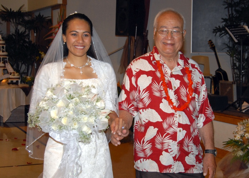 Cesi's father walks her down the aisle at wedding. Bride in white lacy gown, father in red-white aloha shirt. She holds large bouquet of white roses.