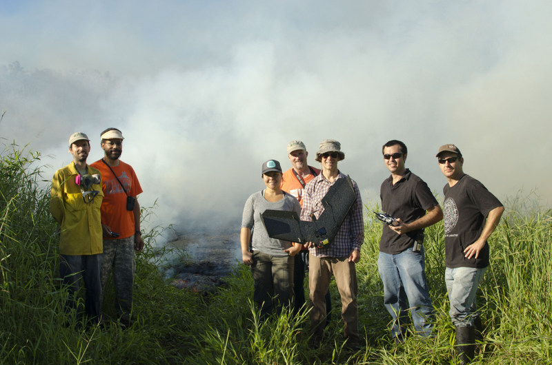 Research team stands for photo in front of an advancing active lava flow. Lots of steam and smoke. Red glowing lava can be seen in some spots of the flow.