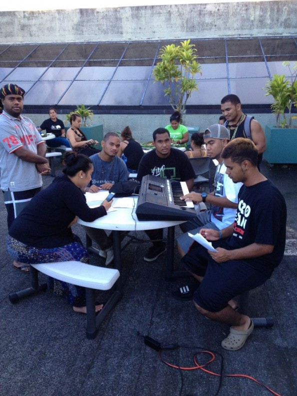 Group of male students gather at table to compose music. One is playing a keyboard.