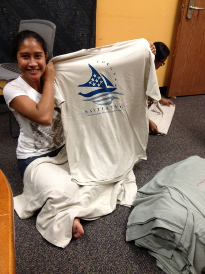 Student holds up t-shirt designed for the event. A sailing canoe with the words: Navigating Success.