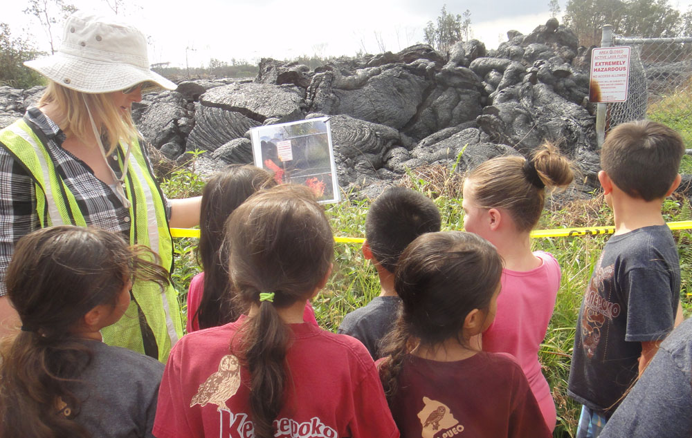 Outside near a recent lava flow, children gather around instructor who is showing them photos of the flow when it was active.