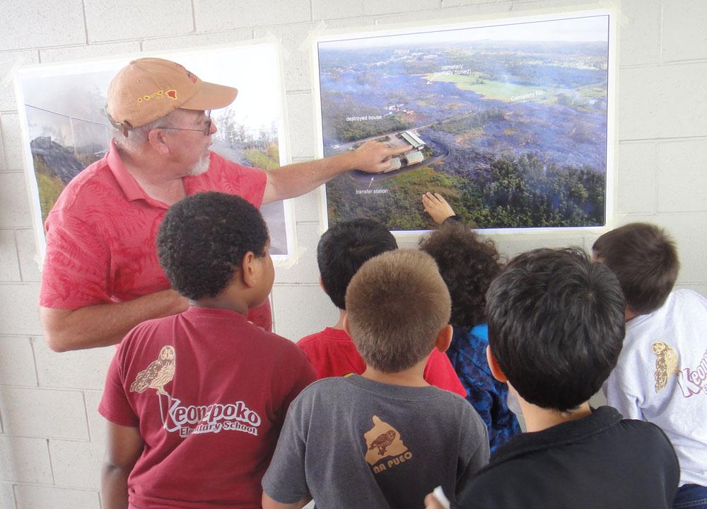 Ken Hon points to photo of lava flow while children gather to listen.