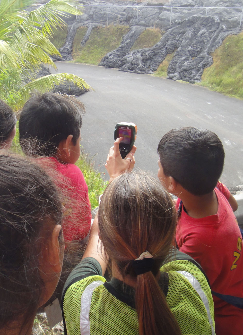 A group of school children  gather while one aims a thermal gun at the lava flow.