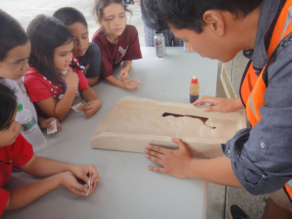 A close up of the mold where five children watch the thick substance flow down the mold. The instructor is at right holding the mold.