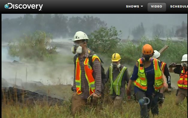 Research team of five people in respirators walk alongside an active lava flow.