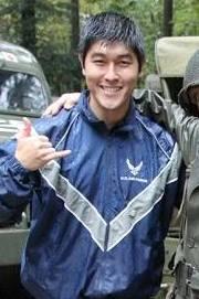 Evan Matsuyama gives the shaka to the camera. He wears a blue rain jacket.