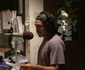 Isaac at a large mic, reading from a piece of paper. He wears headphones.