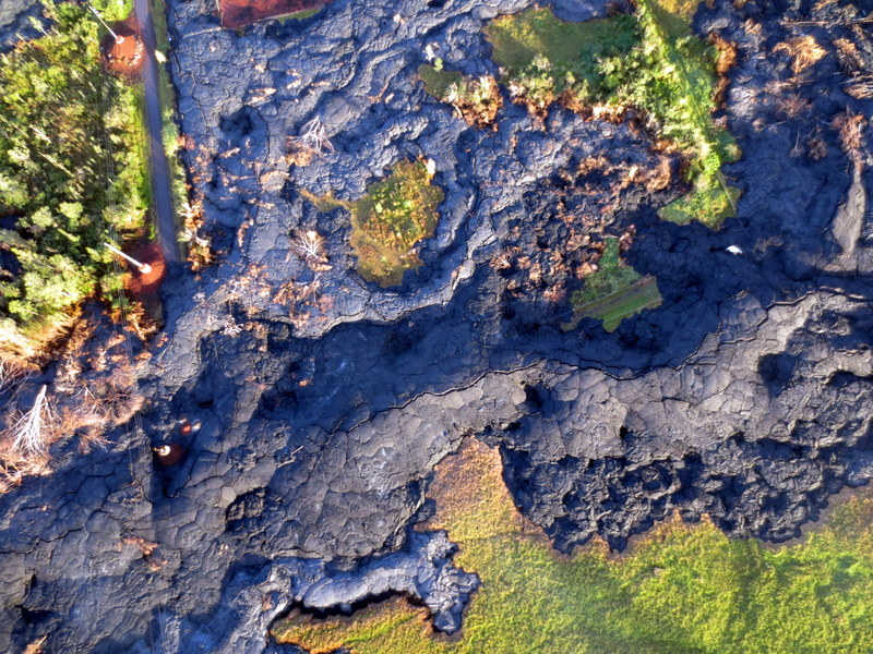 Aerial of lava flow moving through green areas and over road. This tile is used as part of the mosaic.