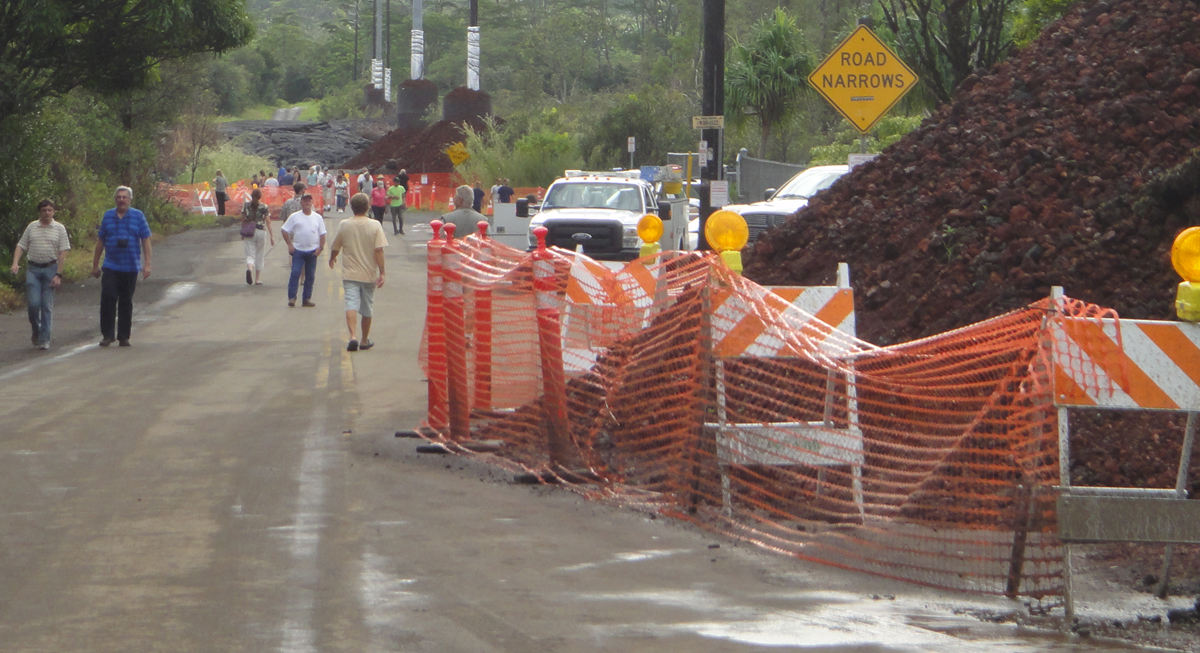 Road with large areas netted off, piles of cinder, people milling around. Sign: Road Narrows.